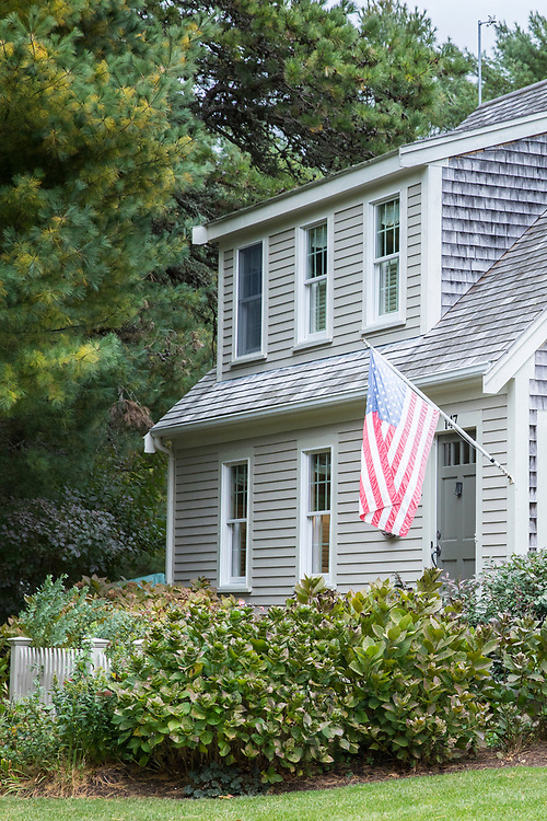 American flag flying and traditional wooden timber clapboard architecture house near Cockle Cove at Chatham, Cape Cod, New England, USA