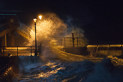 © Licensed to London News Pictures. 14/02/2014. Southsea, Hampshire, UK. A man risking his life by standing on a jetty in Old Portsmouth in Southsea, Hampshire, UK. Strong winds have battered the south coast, with hurricane force 12 winds being forecast. Photo credit : Rob Arnold/LNP