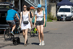 Licensed to London News Pictures. 17/07/2021. London, UK. Walkers enjoy the hot sunshine along the River Thames at Putney Embankment, southwest, London today as weather forecasters predict a very warm and dry Weekend with highs of over 32c in London and the south East with the warm weather lasting up to two weeks. Photo credit: Alex Lentati/LNP