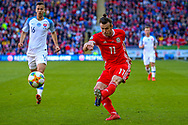 Wales midfielder Gareth Bale crosses the ball during the UEFA European 2020 Qualifier match between Wales and Slovakia at the Cardiff City Stadium, Cardiff, Wales on 24 March 2019.