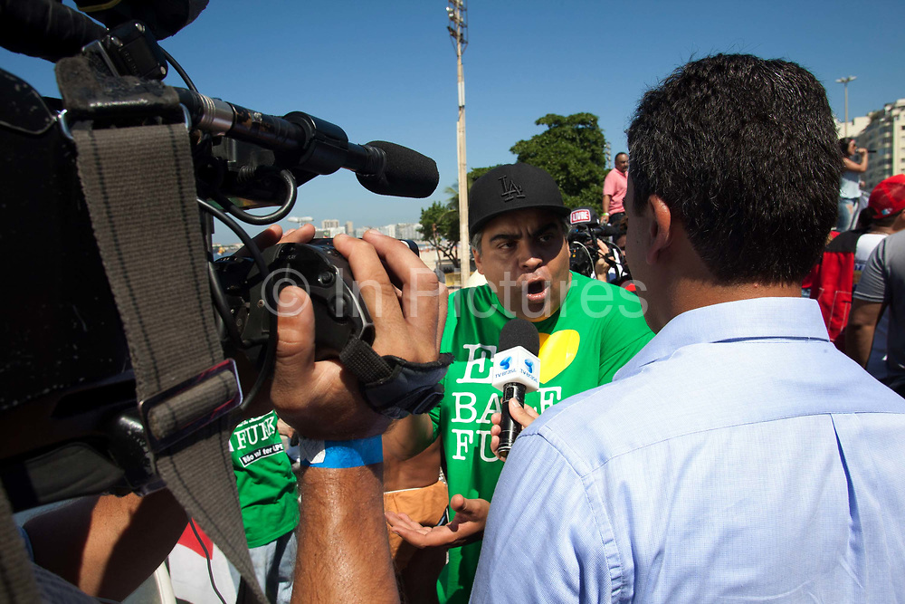 MC Leonardo being interviewed at the anti impeachment protest demonstration on April 17th 2016 in Rio De Janeiro. This was the day of the impeachment vote for Brazils president Dilma Roussef, thousands took to the streets across the country. Here, protests in Copacanbana were held, organised by independent community music organisations Rhythm of the Favela, Apa-funk, Furaco 2000, in associaiton with the Workers Party PT.