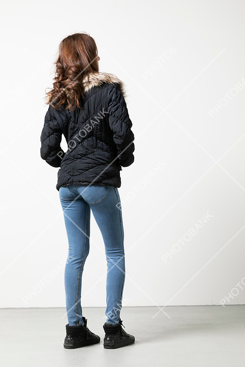 Woman seen from behind standing, whole body. White background