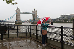 © Licensed to London News Pictures. 30/08/2017. LONDON, UK.  A tourist takes a selfie in front of Tower Bridge during heavy rain showers and wet weather near the Tower of London at lunchtime. Heavy rain is forecast to fall across areas of the country today.  Photo credit: Vickie Flores/LNP