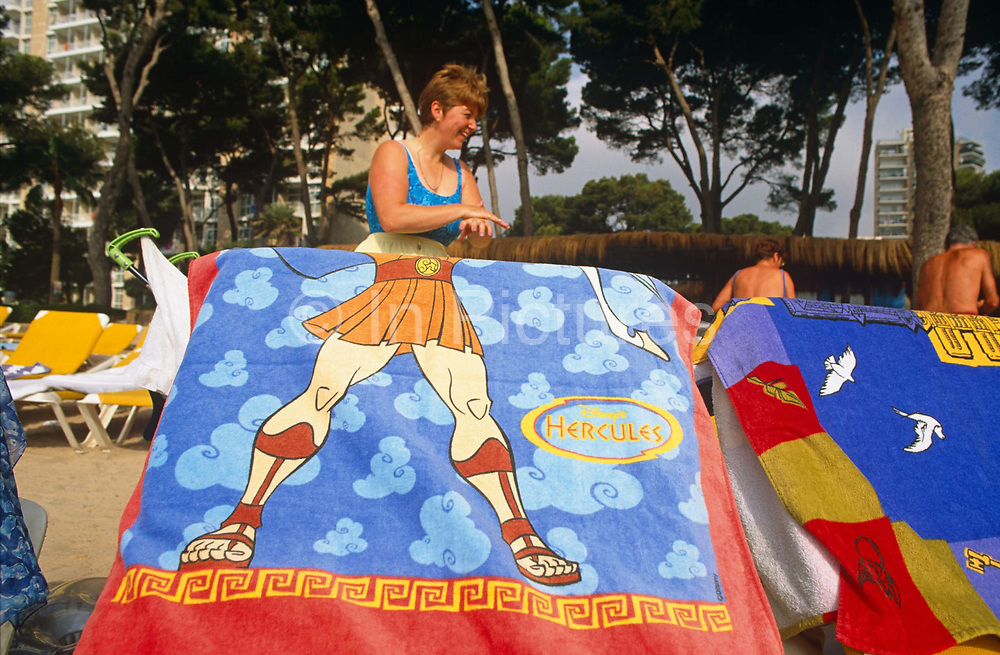 A British lady applies a layer of sun cream to her hand on a beach in Magaluf.  In the foreground, and aligned with the lady's own body is a sun lounger with a beach towel draped over which depicts the torso and legs of a cartoon Hercules Adonis character complete in ancient Greek style with muscular thighs and short skirt. In the background is a hotel building and two other tourists with their tanned backs towards the viewer. Magaluf is a popular holiday resort on the island of Mallorca, one of the Spanish Balearic Islands. A seedy resort very much orientated around British tourists and catering for both young parties as well as families, it is considered as a hot and exotic alternative to the chilly seaside towns around the UK's coast.