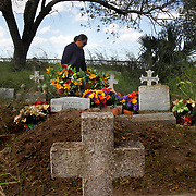 Cecilia Hernandez carries flowers to her relatives' graves while cleaning up their plots for the Day of the Dead holiday on October 24, 2017, at the Santa Rosalia Cemetery in Brownsville. Hernandez' grandparents and many other relatives are buried at the cemetery, which is located south of the border wall just north of the Rio Grande. Nathan Lambrecht/The Monitor
