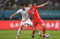 """Billy Bodin, right, of Wales national football team kicks the ball to make a pass against Rodrigo Bentancur of Uruguay national football team in their final match during the 2018 Gree China Cup International Football Championship in Nanning city, south China's Guangxi Zhuang Autonomous Region, 26 March 2018.<br /> <br /> Edinson Cavani's goal in the second half helped Uruguay beat Wales to claim the title of the second edition of China Cup International Football Championship here on Monday (26 March 2018). """"It was a tough match. I'm very satisfied with the result and I think that we can even get better if we didn't suffer from jet lag or injuries. I think the result was very satisfactory,"""" said Uruguay coach Oscar Tabarez. Wales were buoyed by a 6-0 victory over China while Uruguay were fresh from a 2-0 win over the Czech Republic. Uruguay almost took a dream start just 3 minutes into the game as Luis Suarez's shot on Nahitan Nandez cross smacked the upright. Uruguay were dealt a blow on 8 minutes when Jose Gimenez was injured in a challenge and was replaced by Sebastian Coates. Inter Milan's midfielder Matias Vecino of Uruguay also fired at the edge of box from a looped pass but only saw his attempt whistle past the post. Suarez squandered a golden opportunity on 32 minutes when Ashley Williams's wayward backpass sent him clear, but the Barca hitman rattled the woodwork again with goalkeeper Wayne Hennessey well beaten."""