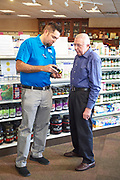 Elderly man getting advice from a pharmacist about supplements.