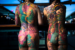 Two women show off their tattoos during the International tattoo convention at Tobacco Dock in east London.