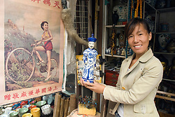 Female shopkeeper holding antique porcelein figure at Dongtai Antiques Market in Shanghai China