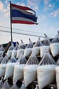 17 JANUARY 2013 - SAMUT SONGKHRAM, SAMUT SONGKHRAM, THAILAND:  A Thai flag flies over bags of salt for sale on the side of the road near Samut Songkhram. The salt was harvested in 2012 and warehoused. The salt fields around Samut Songkhram are some of the most productive salt fields in Thailand. Salt is gathered on a seasonal basis. The fields, which lie near the Gulf of Siam, are flooded with sea water during the last half of the rainy season and then as the water evaporates off after the rainy season migrant workers collect the salt. In 2013 the salt harvest was delayed by months because it continued to rain well after the traditional end of the rainy season.   PHOTO BY JACK KURTZ