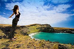 Woman tourist feeling strong wind at Green Sand Beach, Mahana Bay, South Point, Big Island, Hawaii, Pacific Ocean