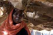 Kalthoum Ibrahim Flamid, 45 has lived in the Abu Shouk refugee camp since having to leave her village in Darfur six years ago. The 4 sq km camp which is (disputedly) home to 38,000 displaced persons and families on the outskirts of the front-line town of Al Fasher (also spelled, Al-Fashir) in north Darfur. Her husband's whereabouts are unknown and she helps look after her children by running this vegetable stall selling tomatoes and onions.
