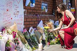 © Licensed to London News Pictures. 20/06/2017. London, UK. A woman leaves flowers outside Finsbury Park Mosque in North London, close to the scene of the attack. A man drove a white van into a crowd of Muslims in Finsbury Park after Ramadan prayers early on the morning of Monday 19 June 2017, killing one man and injuring a number of others. Photo credit: Rob Pinney/LNP