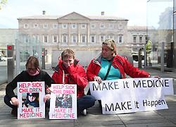 Campaigners for legalising medicinal cannabis Vera Twomey (centre), Sarah Mahoney (left) and Mags O'Sullivan stage a sit down protest inside the gates of Leinster House, Dublin.