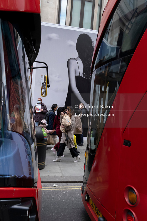 On the day that the UK government eased Covid restrictions to allow non-essential businesses such as shops, pubs, bars, gyms and hairdressers to re-open, buses queue alongside shoppers on Oxford Street and a large fashion retail ad, on 12th April 2021, in London, England.