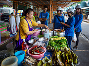 17 SEPTEMBER 2018 - BANGKOK, THAILAND: Construction workers from the ICONSIAM development get lunch from a food stand in the Klong San market, next to the ICONSIAM development. ICONSIAM is a mixed-use development on the Thonburi side of the Chao Phraya River. It is expected to open in 2018 and will include two large malls, with more than 520,000 square meters of retail space, an amusement park, two residential towers and a riverside park. It is the first large scale high end development on the Thonburi side of the river and will feature the first Apple Store in Thailand and the first Takashimaya department store in Thailand. Rents for shopkeepers in Klong San market are up to 30,000 Thai Baht per month (about $920US) and some in Bangkok are concerned that Klong San Market will lose its local character when the huge mall opens.     PHOTO BY JACK KURTZ