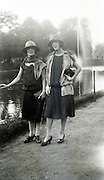 two girls posing by pond with water fountain 1920s