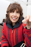 Craftswoman artist holds up one of her heart treasures for sale in her booth. Grand Old Day Festival. St Paul Minnesota MN USA