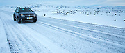 Four wheel drive vehicle - 4 x 4 car - motoring along icy snow-covered road on ring road tourist route in South Iceland