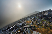 On the summit in dark swirling cloud. A delicate sun glimmered through the vapour, illuminating shards of quartz-covered, shattered wet rock.<br /> .<br /> I was alone on the summit and it helped create the feeling that this pictorial wonder was my privilege alon