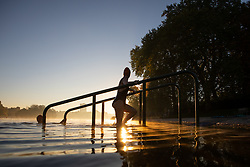 © Licensed to London News Pictures. 27/09/2018. London, UK. A swimmer at the Serpentine Lido in Hyde Park at sunrise this morning. The temperature in the capital is set to reach 22 degrees Celsius later today. Photo credit : Tom Nicholson/LNP