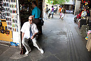 Elderly man smartly dressed rests having a cigarette at a kiosk shop on Athinas. Athens is the capital and largest city of Greece. It dominates the Attica periphery and is one of the world's oldest cities, as its recorded history spans around 3,400 years. Classical Athens was a powerful city-state. A centre for the arts, learning and philosophy.