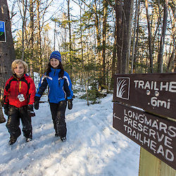 A brother and sister walk on the Sweet Trail in the Society for the Protection of New Hampshire Forest's Dame Forest in Durham, New Hampshire. Winter.