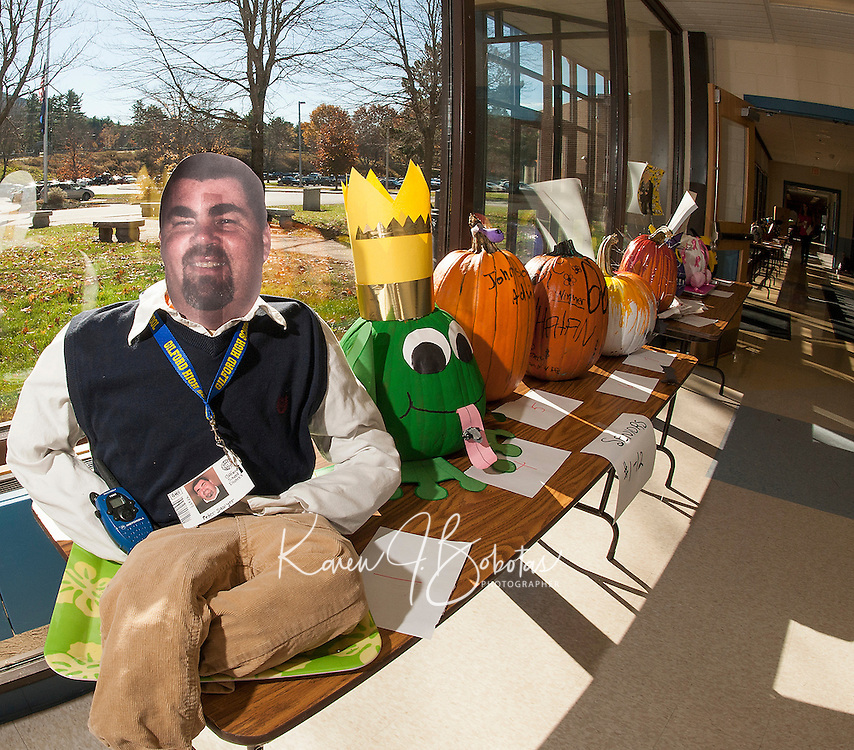 """Gilford High School seniors poke a little fun at their Principal Peter Sawyer with their """"dressed up"""" pumpkin to begin the line of 48 decorated pumpkins in the front hall of Gilford High School awaiting judging down to four finalists.  Students will vote for their top choice out of the finalists in the coming week.  (Karen Bobotas/for the Laconia Daily Sun)"""