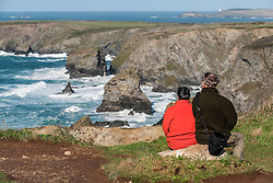 Tourists looking out over Bedruthan Steps in Cornwall.