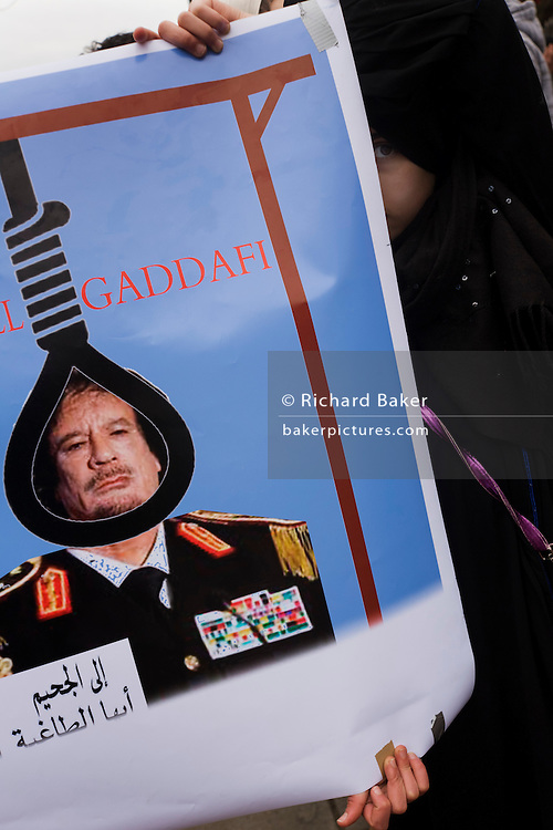 During the Libyan uprising, a young girl in Islamic dress demands the hanging of Colonel Gaddafi during protests opposite London Libyan embassy during the uprising. With another person, she helps hold the placard that shows a caricature of the Libyan dictator wearing a cartoon style chest of medals and with a noose around his neck.