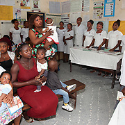 INDIVIDUAL(S) PHOTOGRAPHED: N/A. LOCATION: Epko Abasi Clinic, Calabar, Cross River, Nigeria. CAPTION: Mothers and their young daughters in the waiting room at the Epko Abasi Clinic, listening to the nurses' instructions.