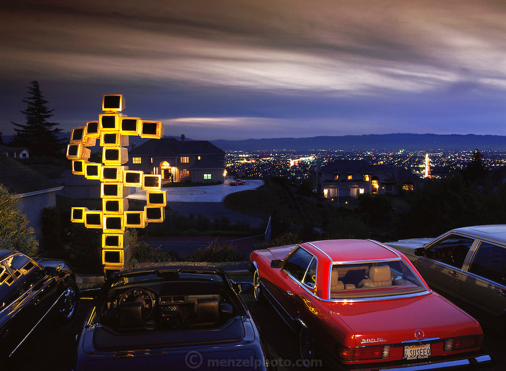 Silicon Valley, California. A sculpture made from recycled computers photographed on Observatory Drive, off Mt. Hamilton Road, overlooking the Silicon Valley and downtown San Jose. The houses in the photos are owned by people in high tech business: a high speed networking company that competes with Cisco, an Apple vice-president, and a software company executive. Neighbors volunteered their cars for the photo: Mercedes, Lexus, Corvette, and a second-car Volvo. After the shoot, the wife of the Apple executive asked that we store the sculpture in the two story atrium of her house where it resided surrounded by a spiral staircase until donated to a museum. (1999).