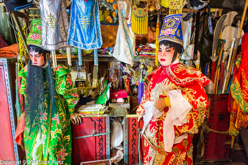 """19 AUGUST 2014 - BANGKOK, THAILAND:  Members of the Lehigh Leng Kaitoung Opera troupe wait to go on stage during a performance at the Chaomae Thapthim Shrine, a small Chinese shrine in a working class neighborhood of Bangkok. The performance was for Ghost Month. Chinese opera was once very popular in Thailand, where it is called """"Ngiew."""" It is usually performed in the Teochew language. Millions of Chinese emigrated to Thailand (then Siam) in the 18th and 19th centuries and brought their culture with them. Recently the popularity of ngiew has faded as people turn to performances of opera on DVD or movies. There are still as many 30 Chinese opera troupes left in Bangkok and its environs. They are especially busy during Chinese New Year and Chinese holiday when they travel from Chinese temple to Chinese temple performing on stages they put up in streets near the temple, sometimes sleeping on hammocks they sling under their stage. Most of the Chinese operas from Bangkok travel to Malaysia for Ghost Month, leaving just a few to perform in Bangkok.        PHOTO BY JACK KURTZ"""