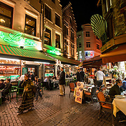 A popular Brussels restaurant specializing in Belgian mussels, Chez Leon on Rue des Bouchers, sits on a narrow cobblestone street along with a street filled with other restaurants popular with tourists.