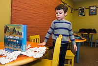 Luke Dorval-Drown cut out snowflakes to bring home during Laconia Library's preschool story hour on Wednesday morning.  (Karen Bobotas/for the Laconia Daily Sun)