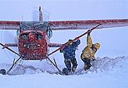 Conrad Anker and Tom Burt help freee a bush plane stucdk in fresh snow on the Ruth Glacier, Denali National Park, Alaska Range, Alaska