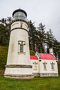 1893 Heceta Head Lightstation, at Heceta Head Lighthouse State Scenic Viewpoint, on the Oregon coast, USA. Here, the Siuslaw Indians traditionally hunted sea lions and gathered sea bird eggs from offshore rocks. While seeking to extend Spanish hegemony in the late 1700s, Spanish explorer Bruno de Heceta mapped the mouth of the Columbia River and much more along the Pacific Northwest coast; and in 1862, the US Coast Survey named Heceta Head in his honor. Built atop a 56-foot tower in 1893, this Lightstation's coastal safety beacon was first illuminated in 1894. Perched 205 feet above the ocean, its fresnel lens focuses the brightest light on the Oregon coast, visible up to 21 miles out to sea. Heceta Head is found halfway between Yachats and Florence (2.1 miles south of Carl Washburne State Park). From the large parking lot, walk 1 mile round trip to the Lighthouse. (Heceta Head Lighthouse State Scenic Viewpoint was created in the 1990s by combining Heceta Head State Park with the former Devils Elbow State Park at the scenic cove at the mouth of Cape Creek.)