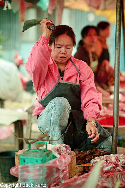 """Mar. 15, 2009 -- LUANG PRABANG, LAOS: A vendor pigs' legs for a customer in the """"morning market"""" in Luang Prabang. The morning market is primarily by local residents for groceries and daily needs. Most Laotians don't have refrigerators so the they shop daily for perishables. Luang Prabang is a UNESCO World Heritage Site and the spiritual capital of Laos. There are dozens of """"wats"""" or temples and thousands of monks in the city. It is still the center of Buddhist education in Laos.  Photo by Jack Kurtz"""