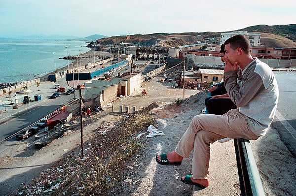 Spanje Ceuta 22-5-2001..Jongeren van Marokkaanse afkomst zitten bij de grensovergang tussen Ceuta en Marokko.Sinds eind 1999 staat een dubbel hek met uitkijktorens om de enclave Ceuta in noord Marokko, teneinde de stroom illegalen en asielzoekers in te dammen. De Guardia Civil kan de grens nu makkelijker controleren. Sindsdien is het aantal binnenkomers sterk gedaald, en probeert men met rubber bootjes het Spaanse vasteland te bereiken.Foto: Flip Franssen