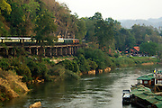 The Orient Express winds along an original River Kwai railroad track, laid by POW's under Japanese occupation. Kanchanaburi, Thailand