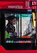 Bus driver wearing a protective mask in a deserted Oxford Circus at rush hour during the Coronavirus pandemic on 26th March 2020 in London, United Kingdom. Several bus drivers have died as a result of COVID-19. Transport union leaders have criticised a bus company for only providing movable shower curtains as barriers to protect drivers from the spread of coronavirus.