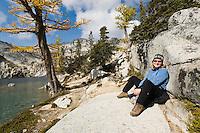 A portrait of a smiling woman sitting next to Perfection lake, Enchantment Lakes Wilderness Area, Washington Cascades, USA.