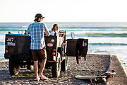 Couple parked in their landrover on the slipway at St Ouen's Bay, Jersey, CI, getting ready to go for a surf at sunset.
