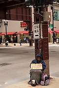 A homeless man begs under the L trains in the Loop District of Chicago, IL.