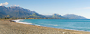 Panoramic view of cobble covered Kaikoura Beach with the Kaikoura Range in the background.