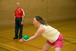 Young woman Day service user catching a ball during an indoor cricket game in the gym,