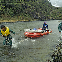 CORDILLERA SARMIENTO EXPEDEDITION, Patagonia, Chile. Team recovers capsized raft in high winds & rain while loading boat at end of expedition.
