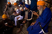 Sikh men eat evening meal on the floor of the Golden Temple's Langar, Amritsar, Punjab, India
