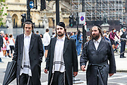"""Three Jewish men walk by the Winston Churchill monument in central London on Sunday, Aug 16, 2020 - as people called from """"All Black Lives UK"""" carrying banners, placards and flags gather to protest against police brutality outside the Houses of Parliament in London on Sunday, Aug 16, 2020. Black Lives Matter enters the 12th weekend of continuous demonstrations against racial injustice in Britain. (VXP Photo/ Vudi Xhymshiti)"""
