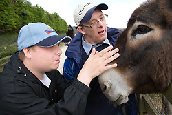 Two men with learning disabilities on a trip to an animal centre stroking a donkey,